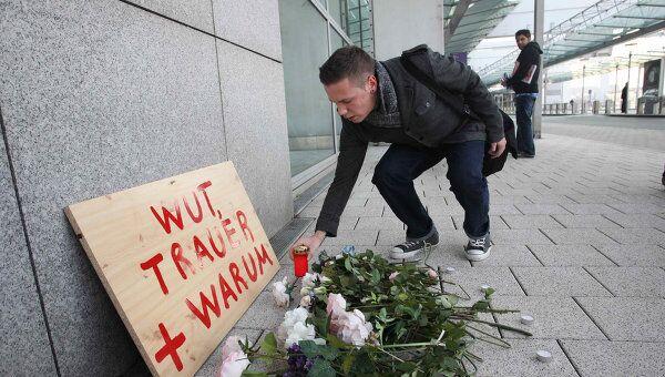 Люди кладут цветы возле места убийства в аэропорту Франкфурта
