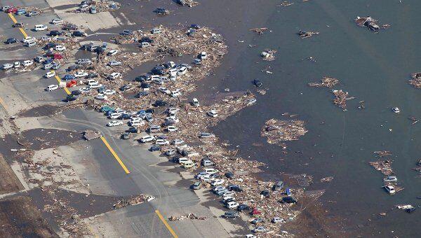 Затопленные в результате землетрясения автомобили в столице префектуры Мияги г.Сендай