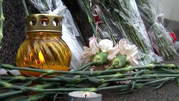 Люди несут живые цветы и свечи к посольству Японии в Москве