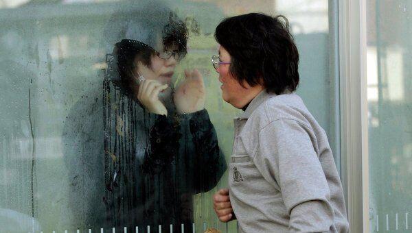 Японская девушка, которая получила повышенную дозу, общается через свинцовое стекло со своими родственниками