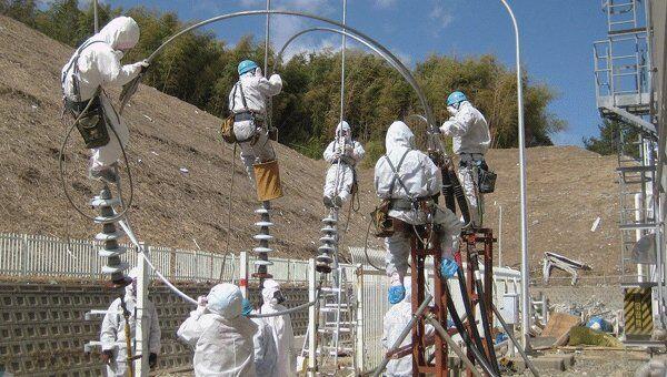 Работники Tokyo Electric Power Co. ремонтируют ЛЭП на японской АЭС Фукусима-1