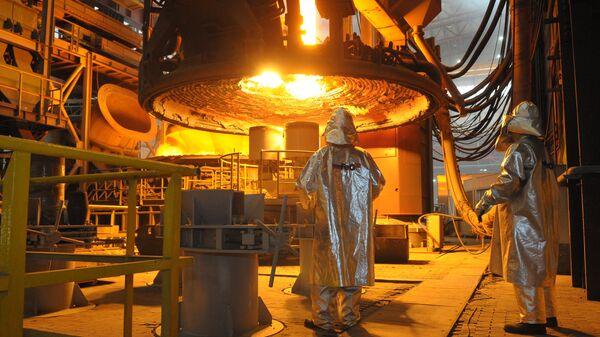 Металлурги следят за процессом загрузки металлического лома в печь