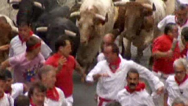 Люди соревнуются с быками в беге на испанском фестивале Сан Фермин