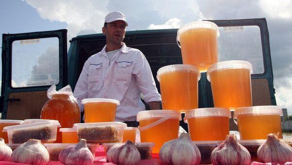 Торговец продает мед и чеснок на ярмарке продовольственных товаров