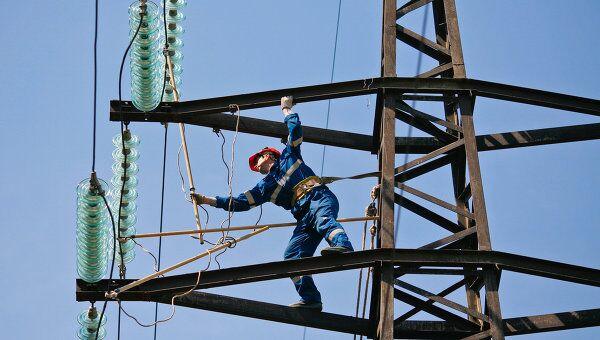 Монтажник проводит плановый ремонт на линии электропередач. Архив