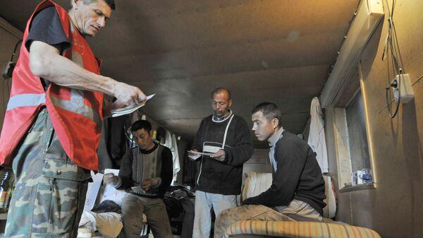 Сотрудники Федеральной миграционной службы проверяют документы у иностранных рабочих, архивное фото