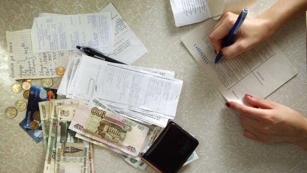 Женщина заполняет квитанцию на оплату коммунальных платежей. Архивное фото
