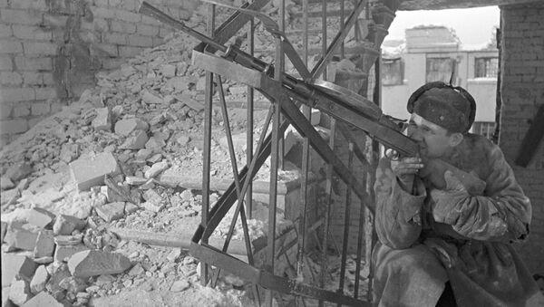 Боец стреляет из ручного пулемета на лестничной клетке разрушенного дома. Битва за Сталинград