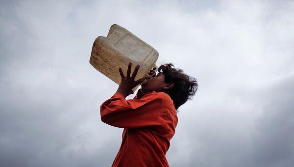 Мальчик пьет воду из канистры на фоне муссоных облаков в городе Карачи