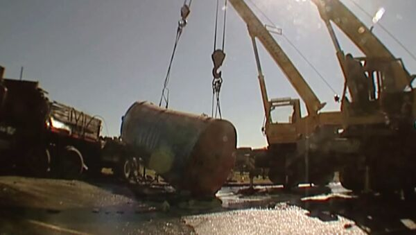 Спасатели поднимают перевернувшуюся емкость с топливом автокраном
