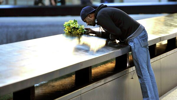Мужчина кладет цветы на мемориальную плиту в Нью-Йорке в честь памяти жертв теракта 11 сентября