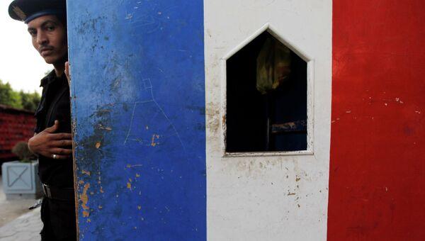 Полицейский охраняет вход в посольство Франции в Каире