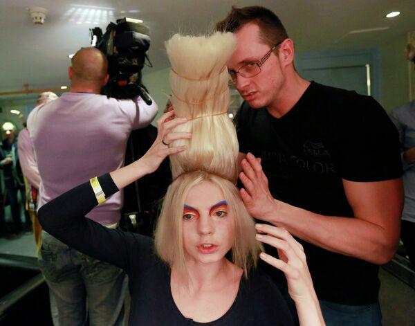 Стилист работает с моделью на шоу Alternative Hair Show в Лондоне