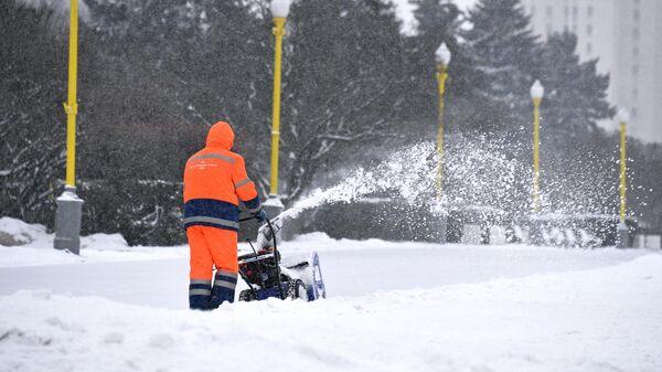Сотрудник коммунальной службы убирает снег с помощью снегоуборочной машины возле здания МГУ на Воробьевых горах в Москве