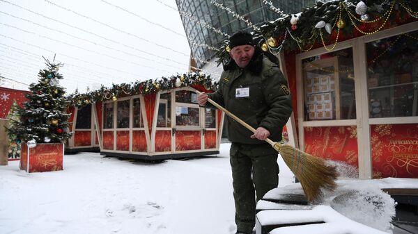 Мужчина убирает снег на площадке фестиваля Путешествие в Рождество в Москве