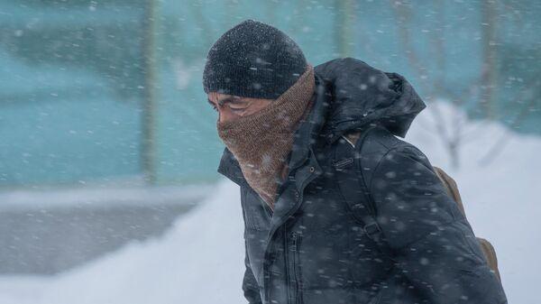 Мужчина идет по улице во время снежной метели в Нур-Султане.