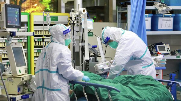 Медицинский персонал в защитных костюмах  в больнице университета Ухань