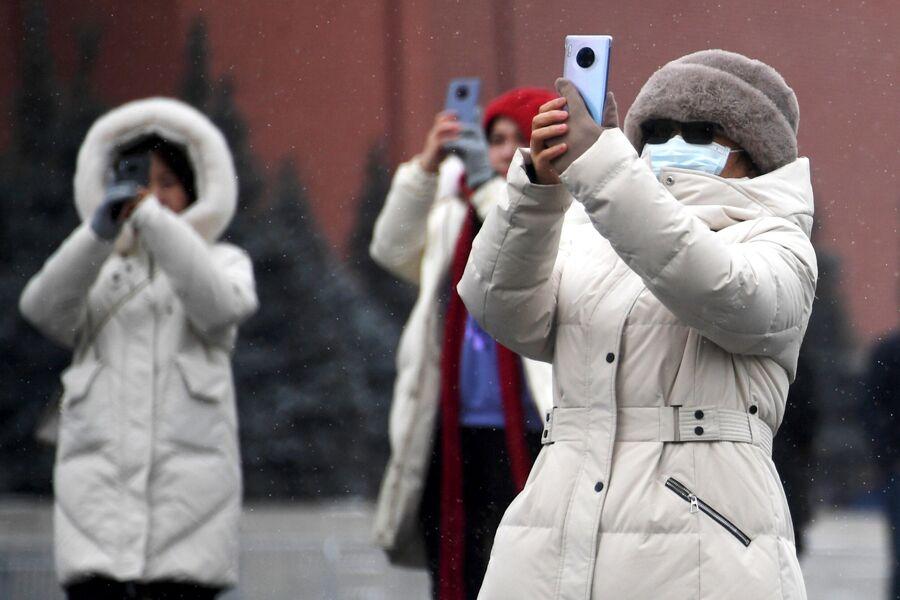 Иностранные туристы в защитных масках на Красной площади в Москве