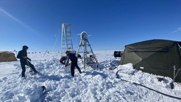 Ученые из Нью-Йоркского университета и Центра глобального изменения уровня моря в Абу-Даби откапывают буровую площадку после снегопада