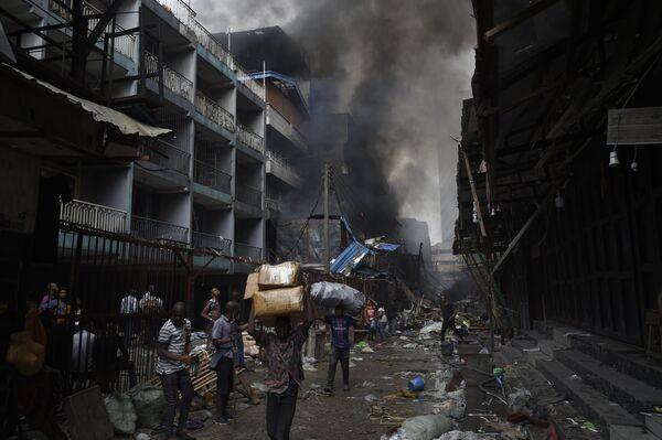 Люди несут товары, спасенные от пожара, в районе рынка Балогун в Лагосе