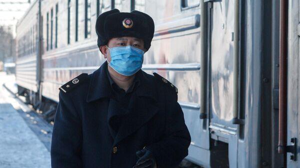 Проводник у вагона поезда Пекин-Москва на железнодорожном вокзале Иркутск-Пассажирский
