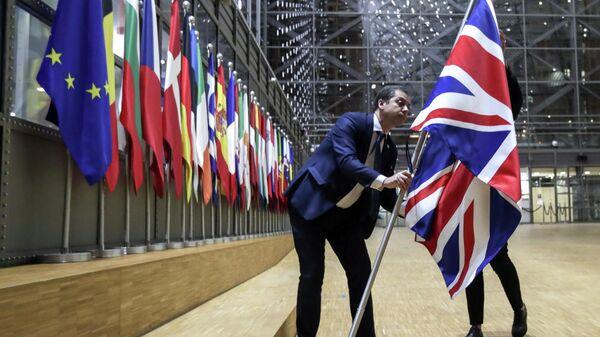 Сотрудники протокола убирают флаг Великобритании у здания Европы в Брюсселе