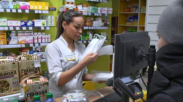 Сотрудник аптеки продает медицинские маски