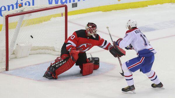 Нападающий ХК Монреаль Илья Ковальчук (справа) и вратарь ХК Нью-Джерси Девилз Луис Доменг в матче регулярного чемпионата НХЛ