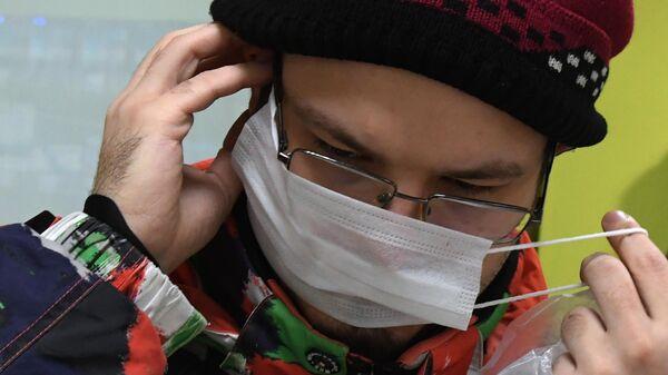 Покупатель надевает защитную маску, купленную в аптеке