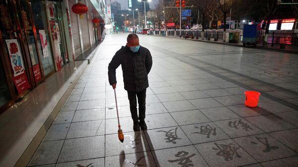 Мужчина рисует иероглифы на тротуаре в китайском городе Цзюцзян