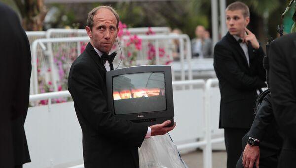 Служитель на дорожке держит работающий телевизор, где идет трансляция церемонии перед премьерой фильма Всего 17