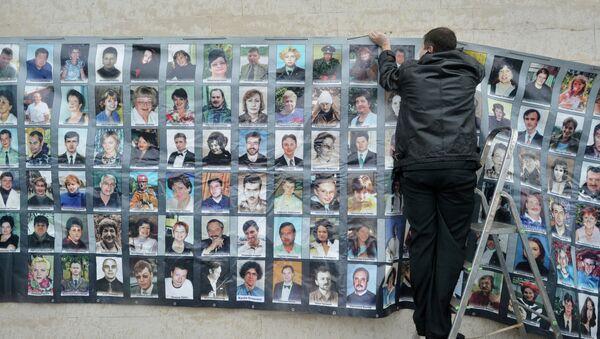 Мужчина вешает фотографии в день памяти по погибшим в результате теракта на Дубровке