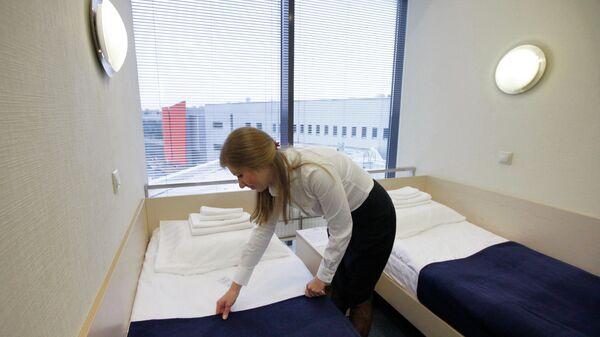 Горничная застилает постель в номере отеля, архивное фото