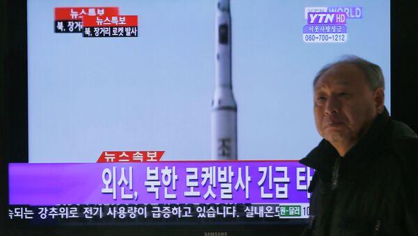 Житель Сеула наблюдает за запуском ракеты-носителя Ынха-3 со спутником Кванмёнсон-3 с космодрома Сохэ