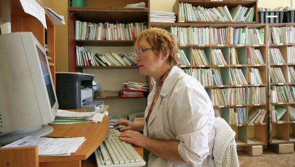 Сотрудница амбулатории работает за компьютером. Архив