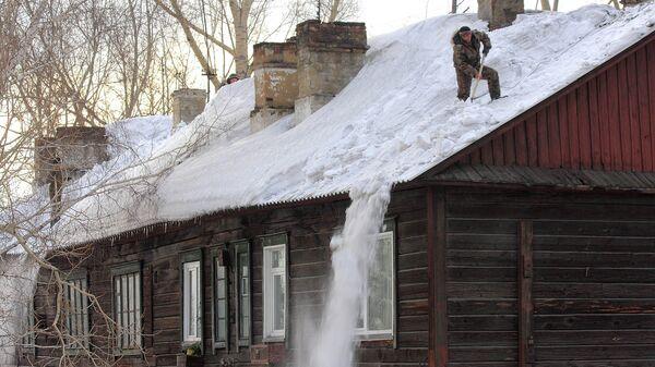 Коммунальщики счищают снег в Новосибирске рядом с домом, где рухнула крыша