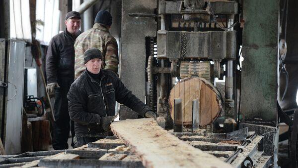Рабочий контролирует процесс распила круглого леса. Архивное фото