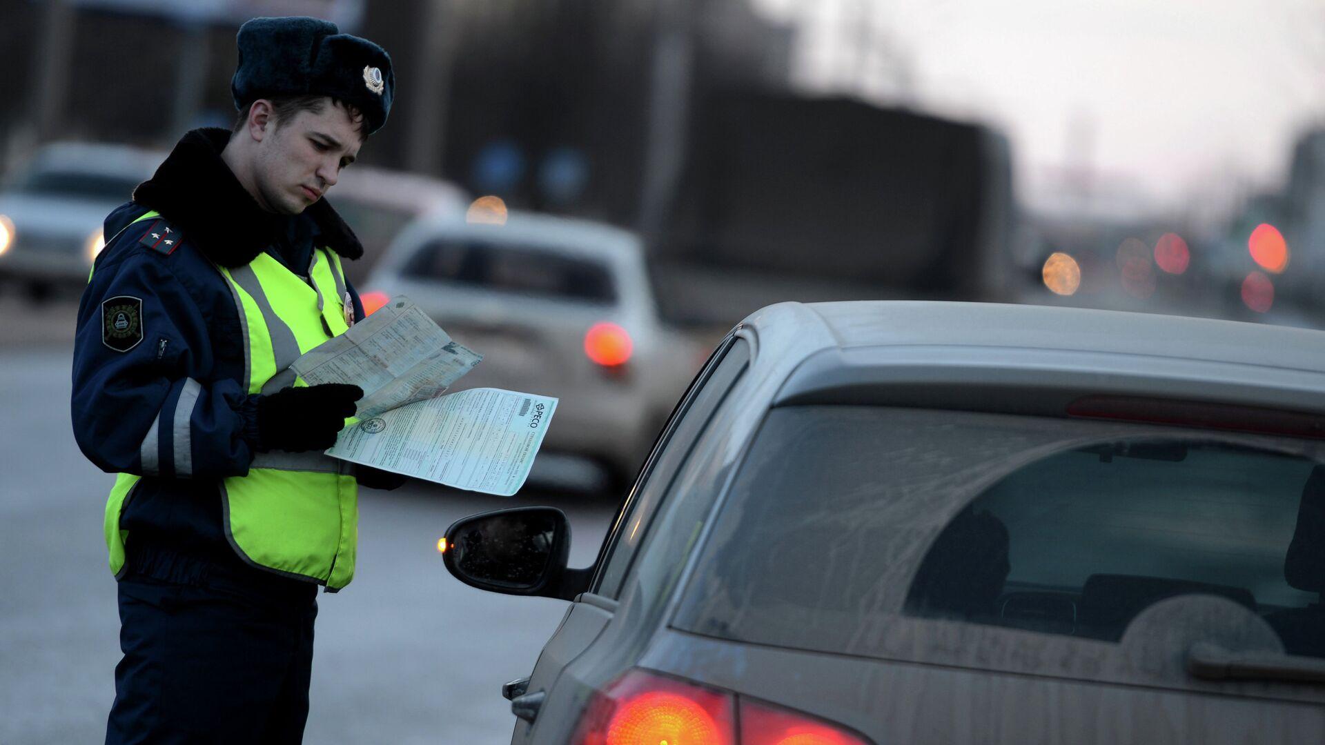 Сотрудник дорожно-патрульной службы ГИБДД проверяет документы у водителя автомобиля - РИА Новости, 1920, 06.01.2021