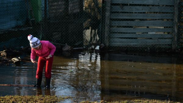 Девочка играет во дворе подтопленного дома