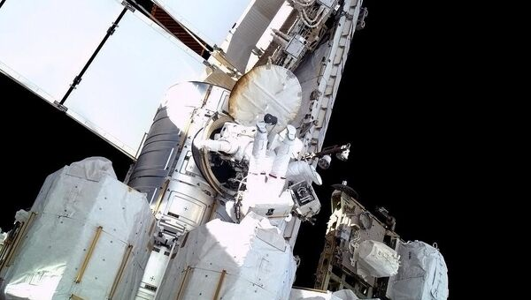 Астронавты Крис Кэссиди и Том Машберн заходят в люк шлюзового модуля Quest после выхода в открытый космос для ликвидации утечки аммиака