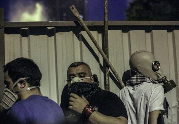 Протестующие прячутся от полиции за забором во время столкновения в Стамбуле