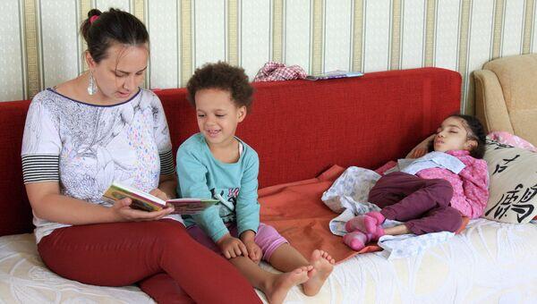 Социальный работник фонда Паллиативная помощь детям Наталья Малкина читает книжку Куне и Джулии