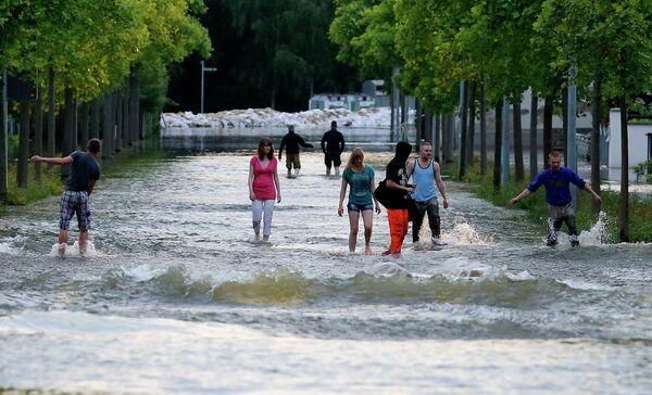 Люди идут по затопленной улице в городе Магдебург, Германия