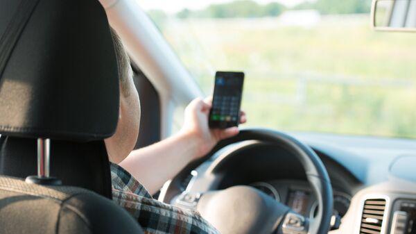 Молодой человек пользуется мобильным телефоном за рулем автомобиля