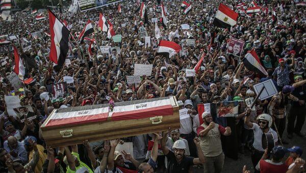 Участники митинга сторонников президента Мохаммеда Мурси держат картонные гробы, символизирующие погибших в столкновениях с армией