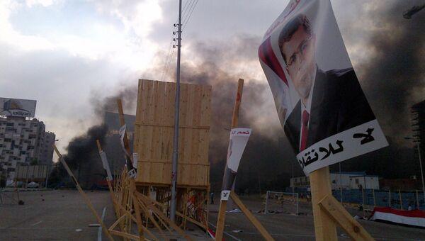 Плакат Мохаммеда Мурси на фоне дыма, где идет разгон лагеря исламистов