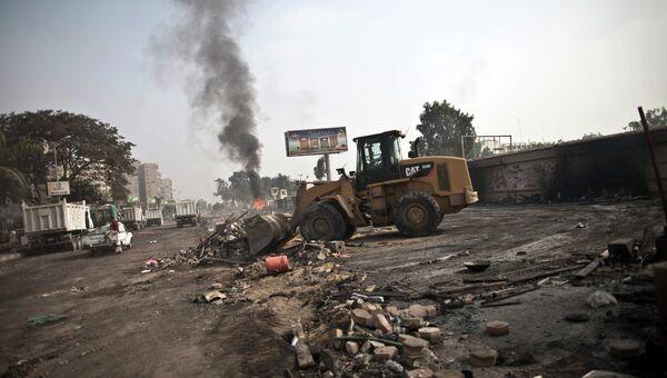 Трактор очищает улицу после столкновений в Каире