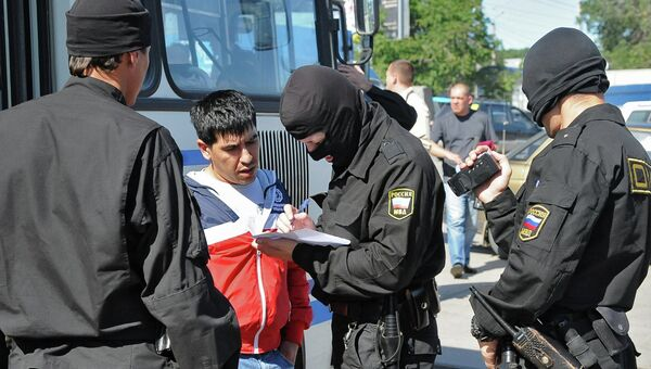 Сотрудник ОМОН регистрируют задержанного во время рейда на одном из рынков