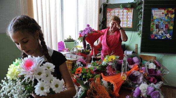 Учительница с букетами цветов в первый день нового учебного года в гимназии Читы