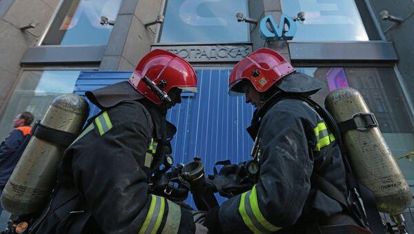 Сотрудники пожарной службы МЧС России работают у вход в вестибюль станции метро Петроградская в Петербурге. Фото с места события